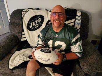 Howie Assa holding his autographed Joe Namath football
