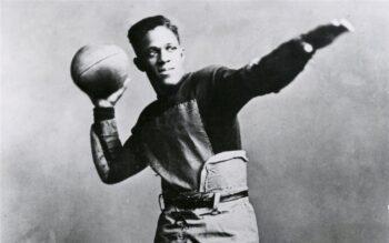 Fritz Pollard of Akron Pros holding a football