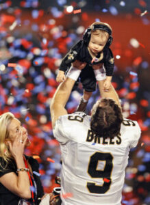 Drew Brees raises his son overhead after defeating the Indianapolis Colts in Super Bowl XLIV